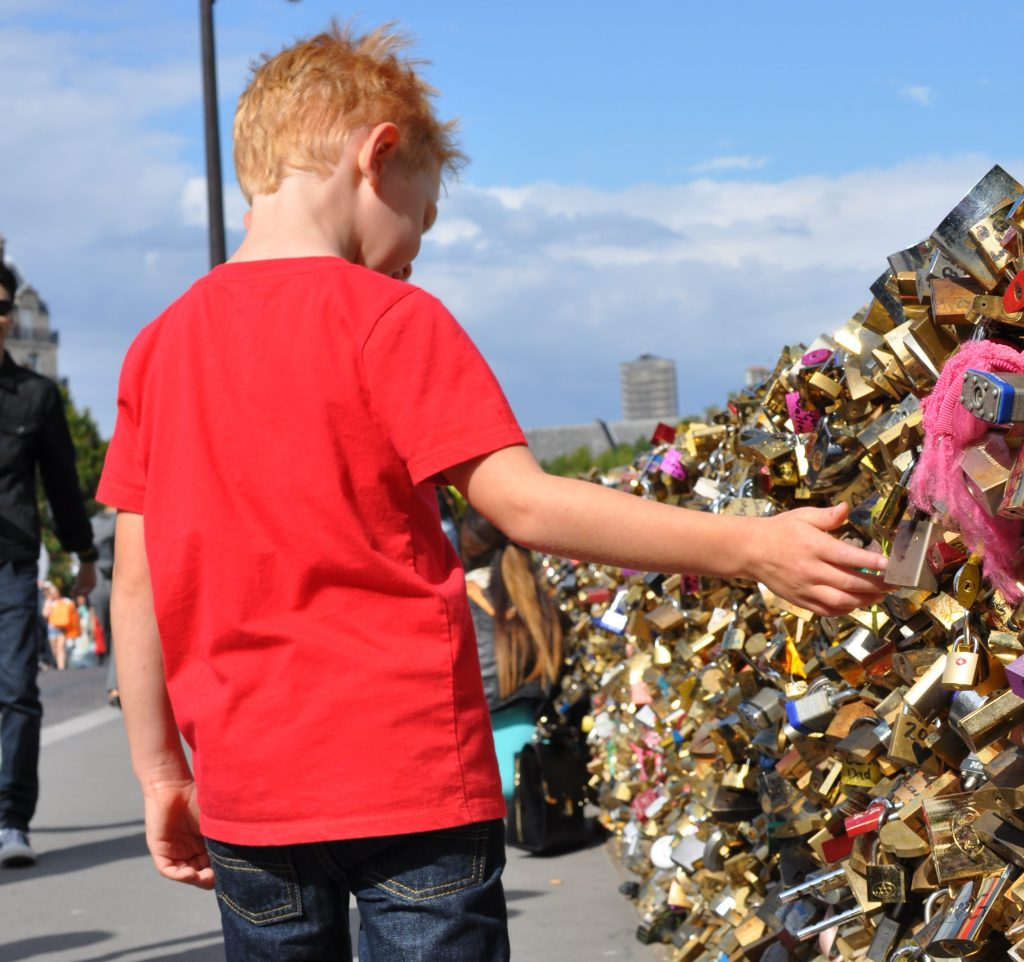 boy looking at locks on the fence